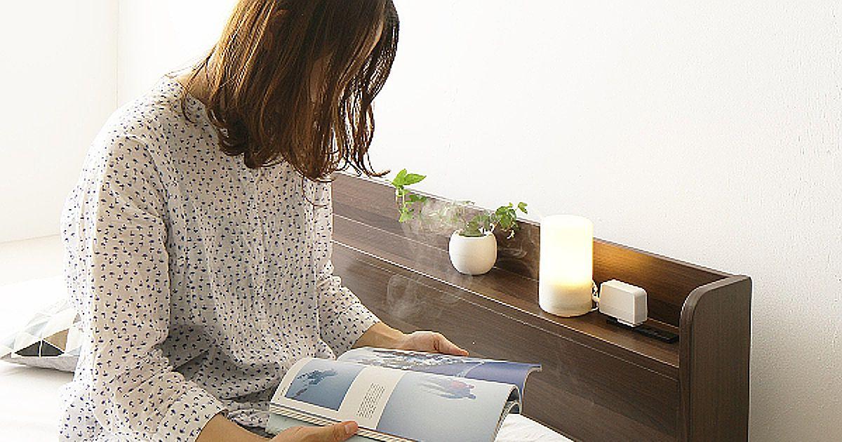 一人暮らしの女性がベッドで雑誌を読む