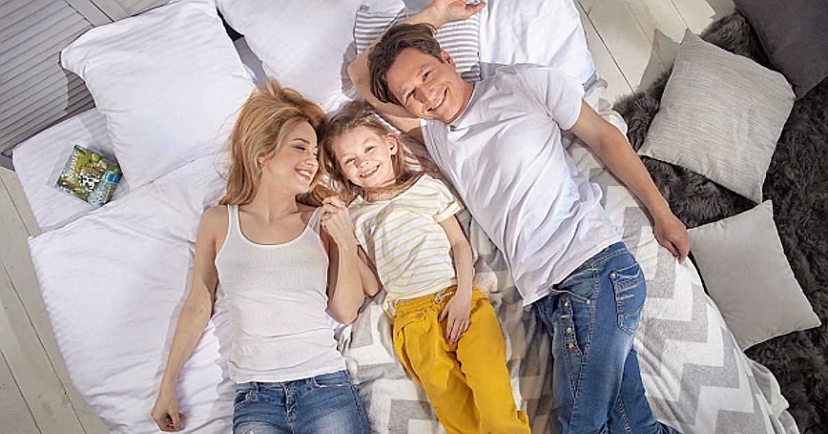 ベッドに寝転がる3人の親子