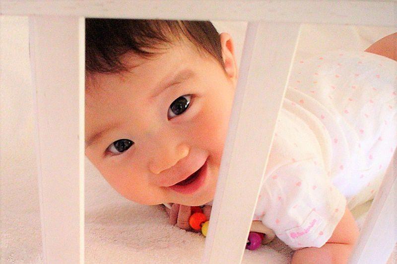 ベビーベッドから覗く赤ちゃん