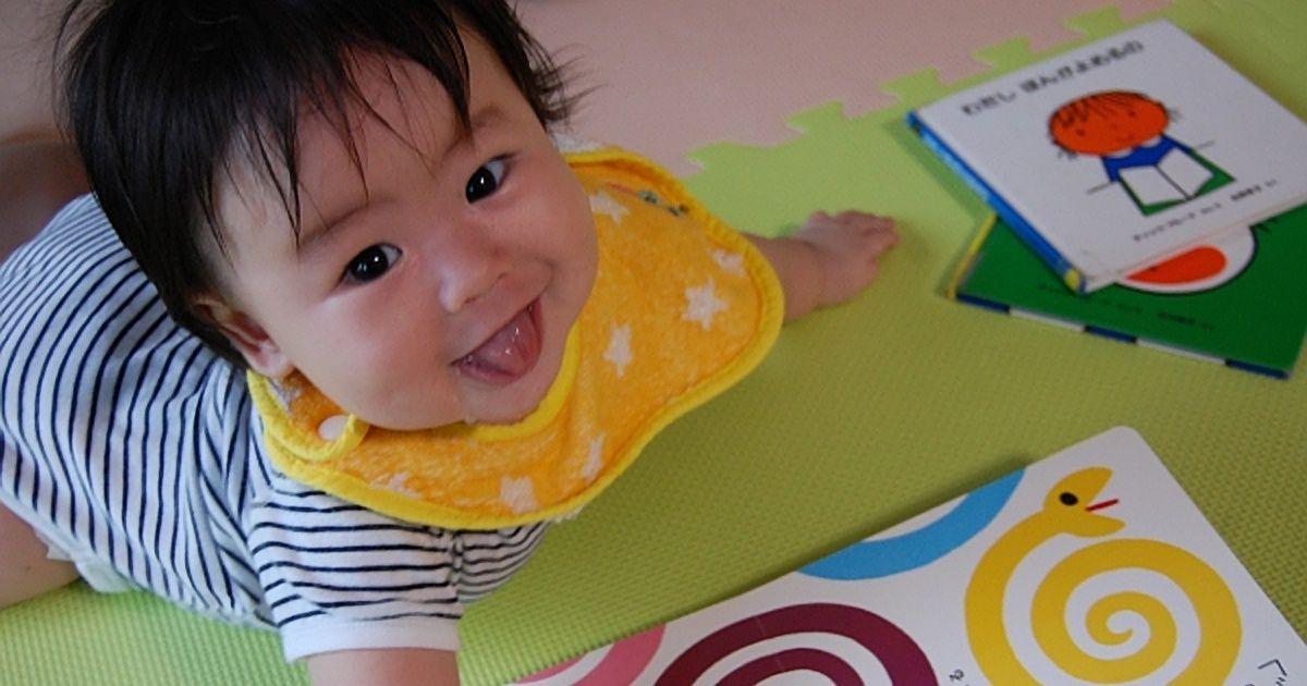 ジョイントマットの上で絵本を読む赤ちゃん