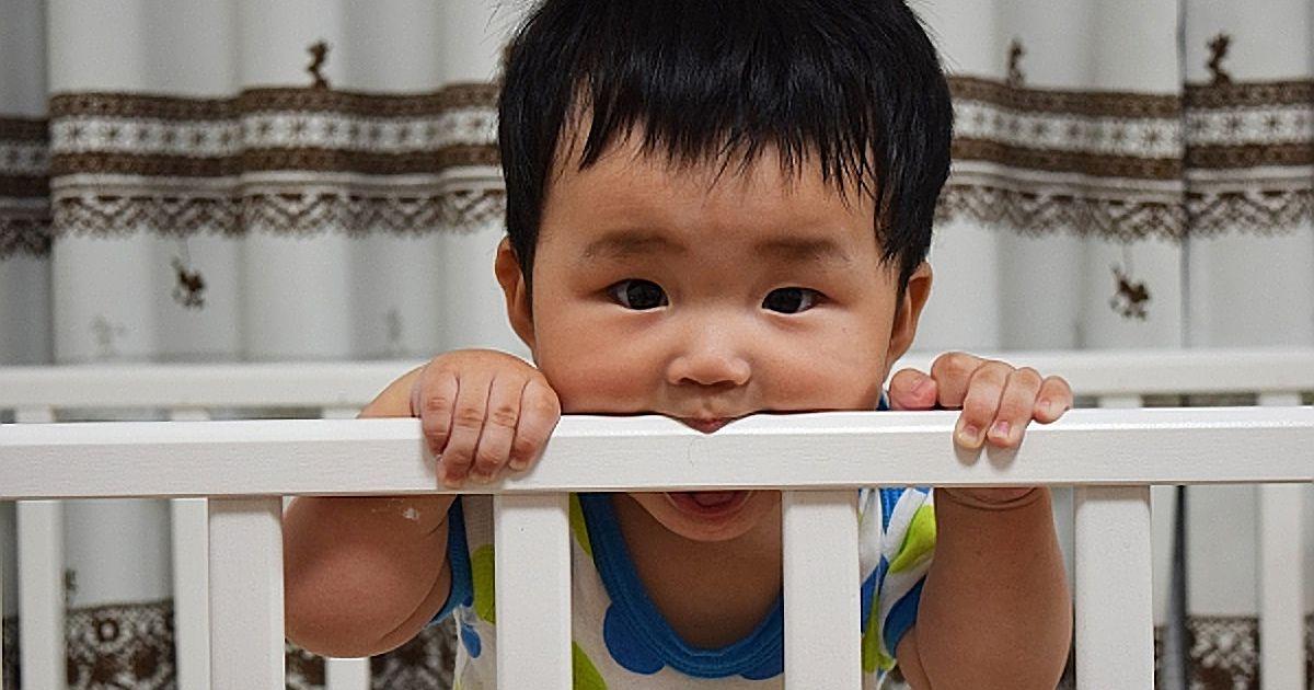 ベビーベッドを噛む赤ちゃん